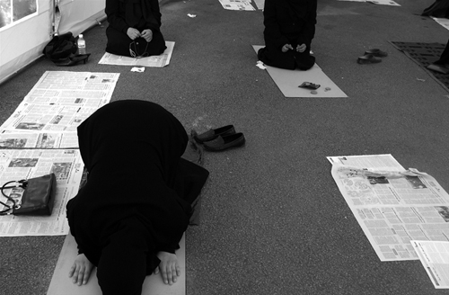 Women-praying-on-newspaper.jpg